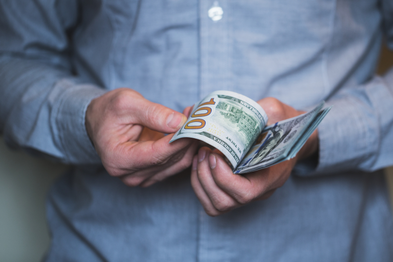 Businessman-holding-money-in-his-hands-PQRBNZW